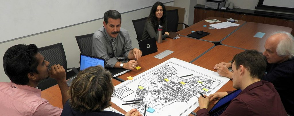 A committee sitting around a conference table looking at a map of campus.